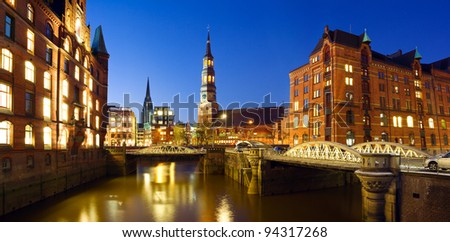 Warehouse district ( Speicherstadt ) of Hamburg at night with view towards the city center including the St. Catherine's Church and St. Nikolai - stock photo