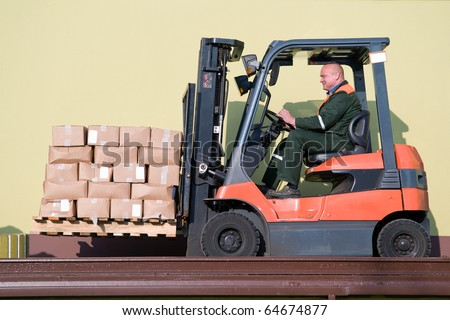 warehouse forklift loader with cardboard freight moving on a ramp - stock photo
