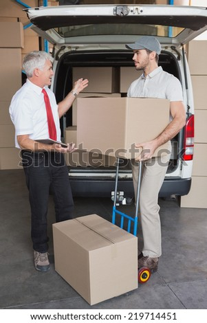Warehouse manager and delivery driver talking beside van in a large warehouse - stock photo