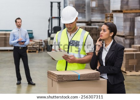 Warehouse manager and worker talking in a large warehouse - stock photo