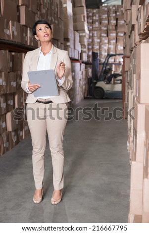 Warehouse manager checking her inventory in a large warehouse - stock photo