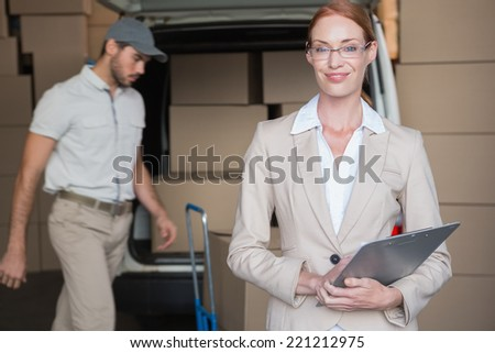 Warehouse manager smiling at camera with delivery in background in a large warehouse - stock photo