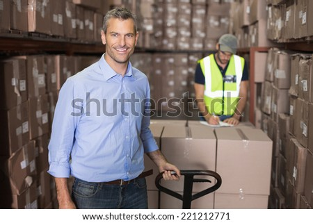 Warehouse manager smiling at camera with trolley in a large warehouse - stock photo