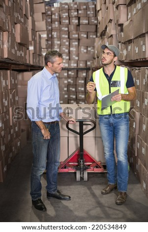 Warehouse manager talking with worker in a large warehouse - stock photo
