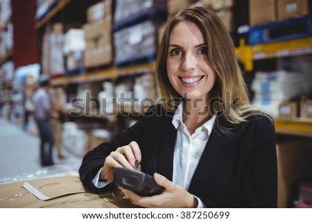 Warehouse manager using scanner and smiling at the camera