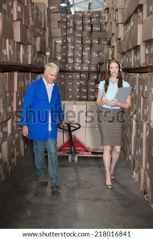Warehouse manager walking with foreman pulling trolley in a large warehouse