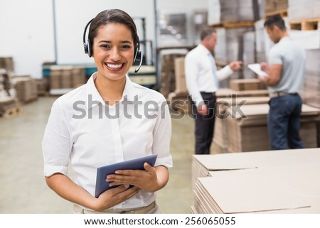 Warehouse manager wearing headset holding clipboard in a large warehouse