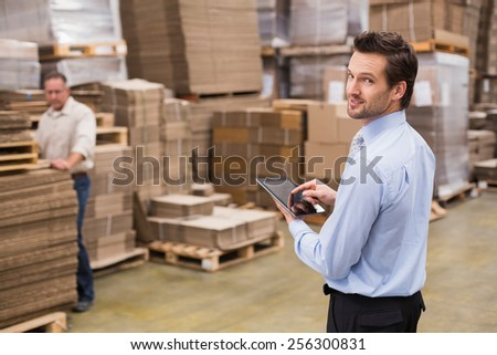 Warehouse manager working on tablet pc in a large warehouse - stock photo