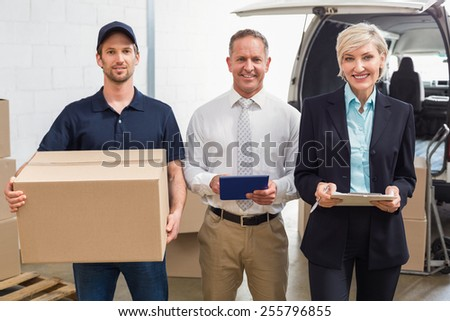 Warehouse managers and delivery driver smiling at camera in a large warehouse