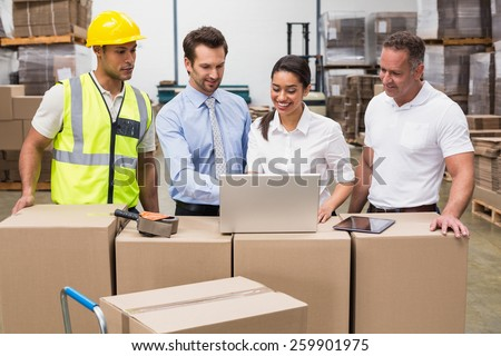 Warehouse managers and worker looking at laptop in a large warehouse - stock photo