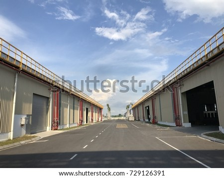 Warehouse outdoor during the sunny day with cloudy blue sky.