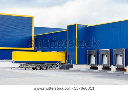warehouse painted yellow and blue with a trailer in front - stock photo