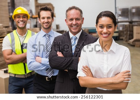 Warehouse team smiling at camera in warehouse - stock photo