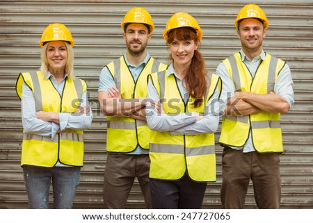 Warehouse team with arms crossed wearing hard hat in a large warehouse - stock photo
