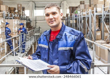 warehouse three workers- one man and two woman in a special blue uniform is recording and accounting of contents in cardboard boxes in stock Idea account statistics rediscount cargo arrival - stock photo