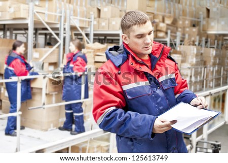 warehouse three workers - one man and two woman in a special uniform is recording and accounting of the contents in cardboard boxes in stock - stock photo