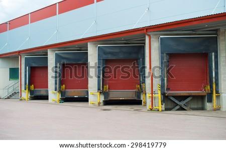 Warehouse with four red sliding gates. - stock photo