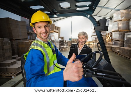 Warehouse worker and his manager smiling at camera in a large warehouse - stock photo