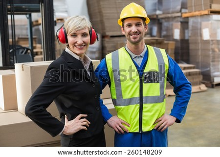 Warehouse worker and his manager with hands on hips in a large warehouse - stock photo