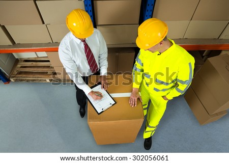 Warehouse Worker And Manager Checking Inventory In Warehouse - stock photo