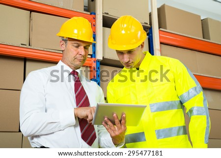 Warehouse Worker And Manager Looking At Laptop In A Large Warehouse - stock photo