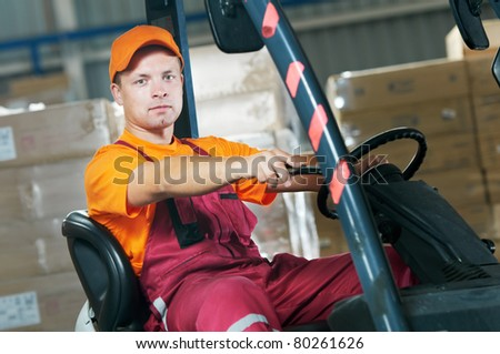 Warehouse worker distributing goods in a storehouse with forklift truck loader - stock photo