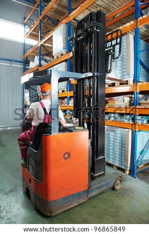 Warehouse worker distributing goods in a storehouse with forklift truck loader stacker - stock photo