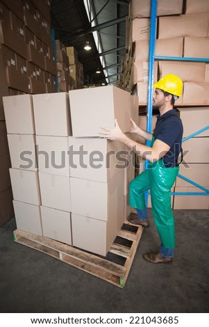 Warehouse worker loading up a pallet in a large warehouse - stock photo