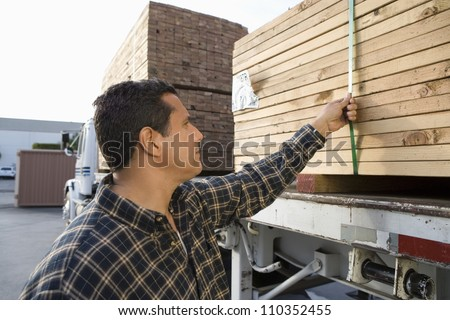 Warehouse worker loading wooden planks on truck carrier - stock photo