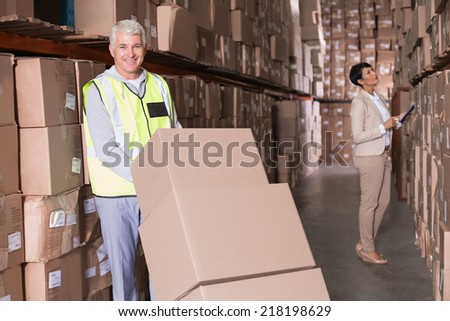 Warehouse worker moving boxes on trolley in a large warehouse - stock photo