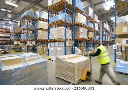 Warehouse worker pushing pallet truck with cardboard boxes - stock photo