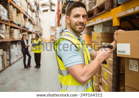 Warehouse worker scanning box while smiling at camera in a large warehouse - stock photo