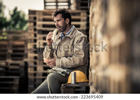 Warehouse worker sitting on pallets for a lunch break - stock photo