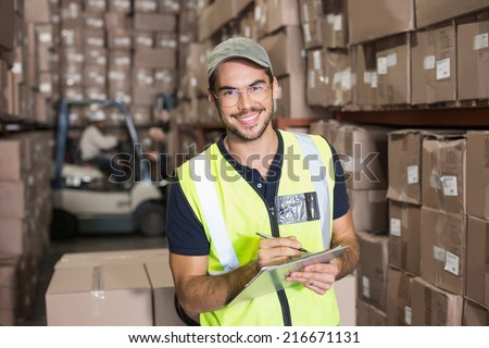 Warehouse worker smiling at camera with clipboard in a large warehouse - stock photo