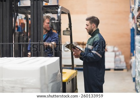 Warehouse worker talking with forklift driver in ware house