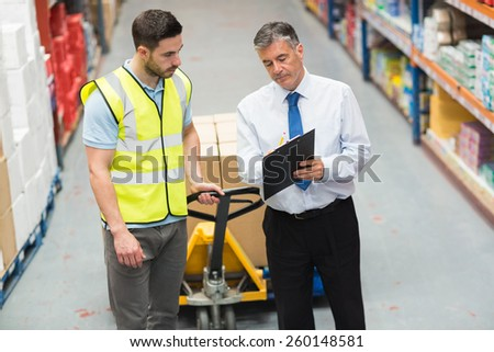 Warehouse worker talking with his manager in a large warehouse - stock photo