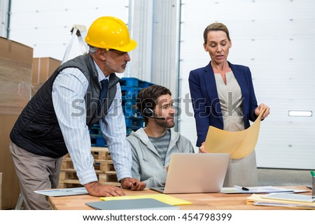 Warehouse worker team looking at document in warehouse office