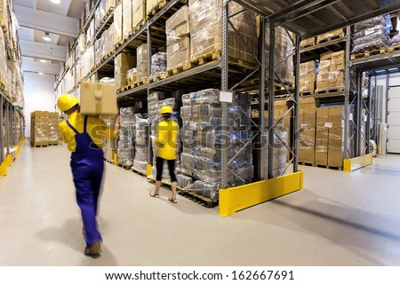 Warehouse worker with box and manager controlling products - stock photo