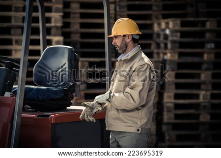 Warehouse worker with fork lift - stock photo