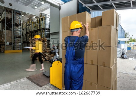 Warehouse workers doing their work - export of packages with articles - stock photo