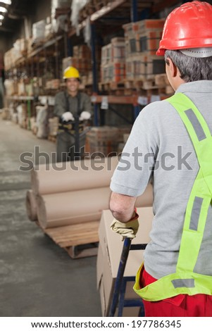 Warehouse workers pushing handtruck stacked with rolled cardboard - stock photo