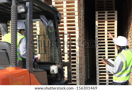 warehouse workers team at unloading works with forklift loader  - stock photo