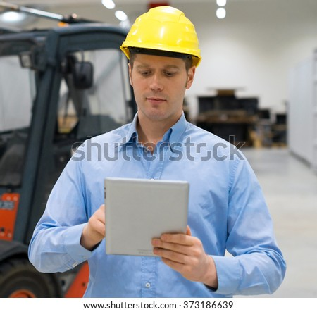 Warehouseman in hard hat with tablet pc at warehouse. - stock photo
