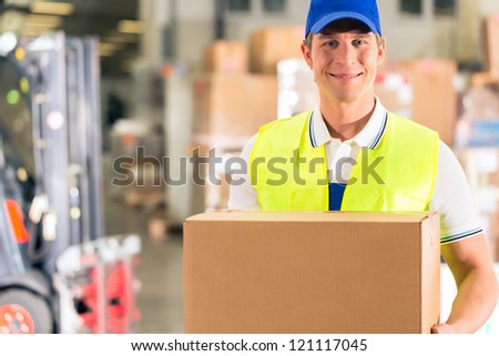 Warehouseman with protective vest holds package, he standing at warehouse of freight forwarding company - stock photo