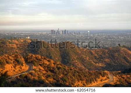 Warm afternoon light and stormy clouds above Griffith Park and downtown Los Angeles. - stock photo