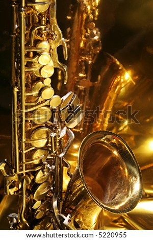Warm and golden lite saxophone against reflective background with copy space - stock photo