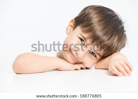 Warm and real smile from preschooler kid lying on the table - stock photo