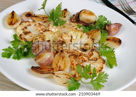 Warm appetizer of fried pieces of cauliflower with garlic and onion - stock photo