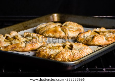Warm apple tarts coming out of the oven - stock photo