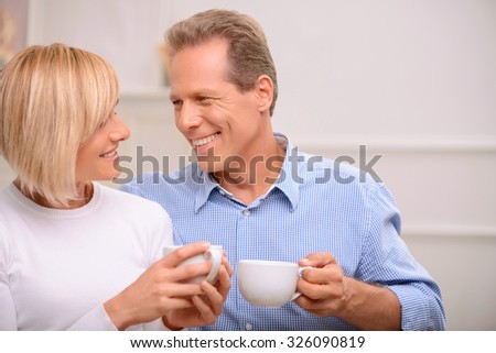 Warm atmosphere. Vivacious agreeable smiling adult couple bonding to each other and drinking coffee while relaxing at home - stock photo